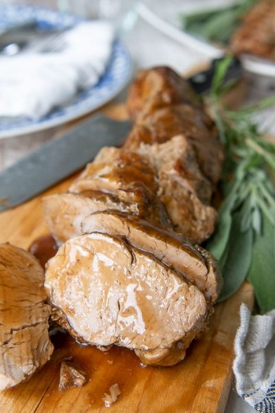 cut pieces of pork tenderloin on a wooden cutting board with sauce drizzled over