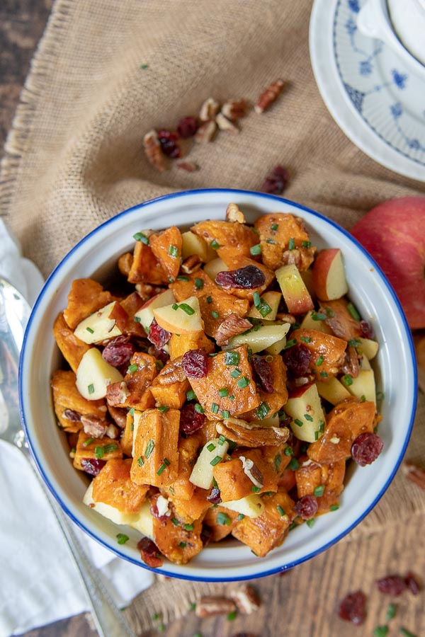 overhead shot of roasted sweet potato salad with a serving spoon and apple resting by