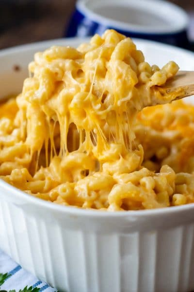 a wooden spoon lifting out cheesy baked velveeta mac and cheese