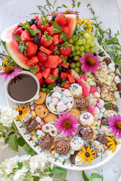 photo a dessert platter on a white tray with fruit, sweets, and fresh flowers