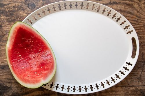 first step of how to make a dessert plate - placing a hollowed out watermelon
