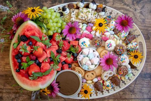 a completed dessert platter with flowers decorating it