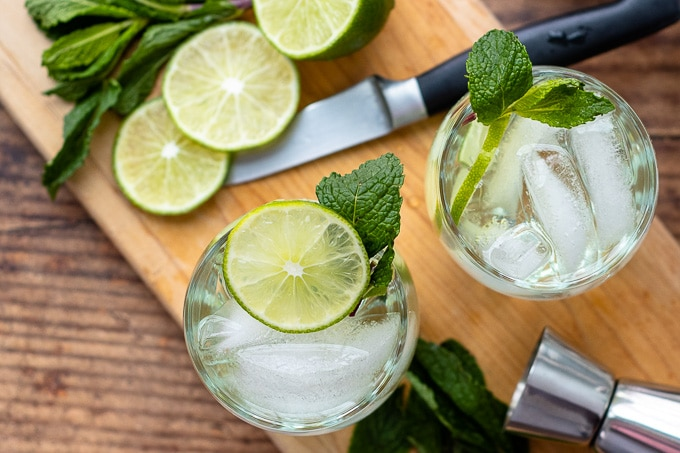 overhead shot of two vodka gimlets on a wooden board with cut limes around them