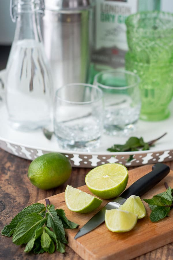 cut limes on a wooden board with the ingredients to make a gimlet cocktail in the background