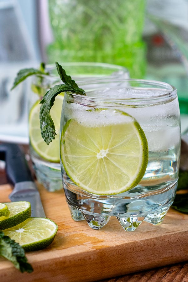two gin gimlets on the rocks on a wooden board with fresh mint sticking out of glass
