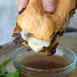 a hand holding french dip sandwich about to be dipped into au jus