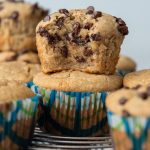 a chocolate chip almond flour muffin with a bite taken out and stacked on another muffin