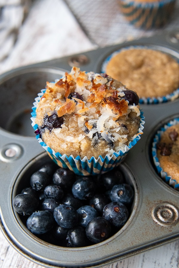 an almond flour blueberry muffin on a tin with blueberries filling one of the cups