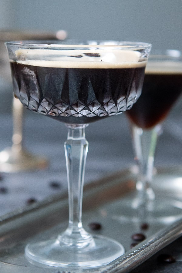 a straight on shot of espresso martini on a silver tray