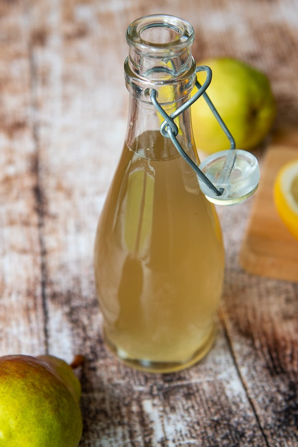 a bottle of ginger simple syrup in a glass bottle with a fresh pear next to it