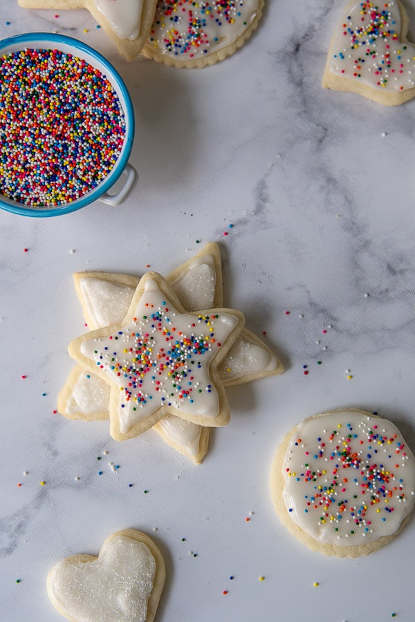 overhead shot of gluten free cut out cookies with a cup of sprinkles nearby