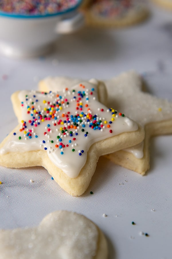 a stack of two star gluten free sugar cookies with white icing and sprinkles on top
