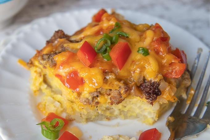a close up of sausage breakfast casserole with hash brown layer on bottom and a bite taken out