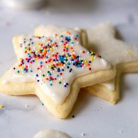 a stack of two star roll out sugar cookies with white icing and sprinkles on top