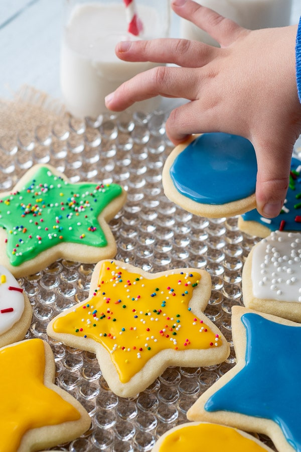 a small hand picking up an iced sugar cookie from a plate