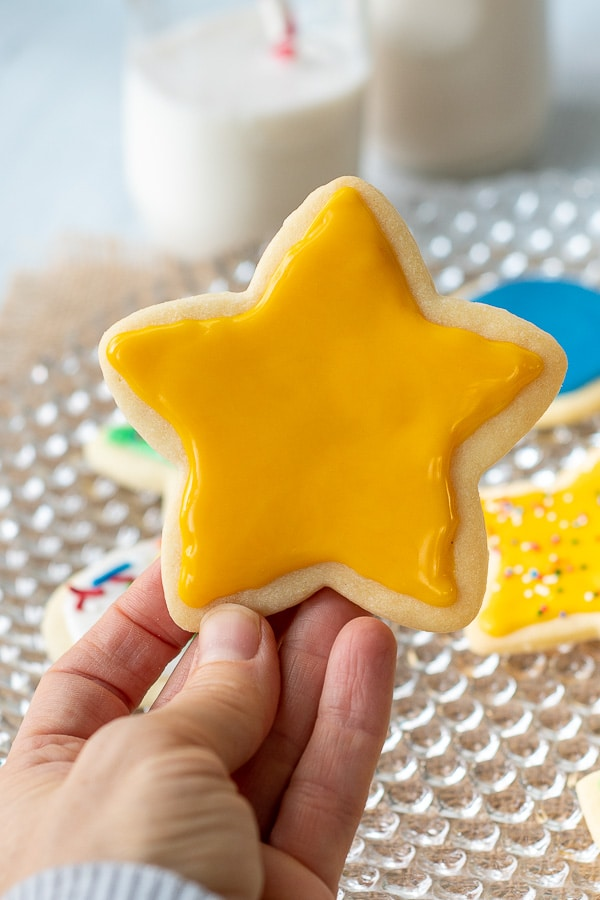 a yellow cut out sugar cookie being held up with sugar frosting that hardens