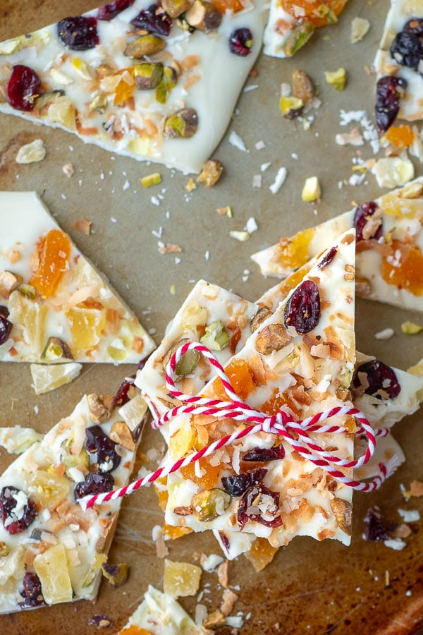 fruit and nut white chocolate bark on a baking sheet with string tied around it