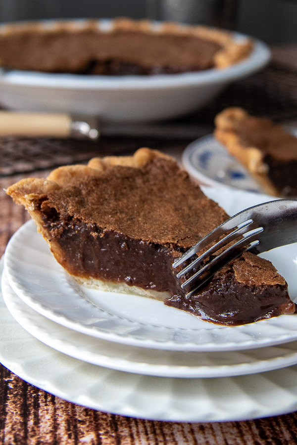 a fork cutting into a piece of chocolate chess pie