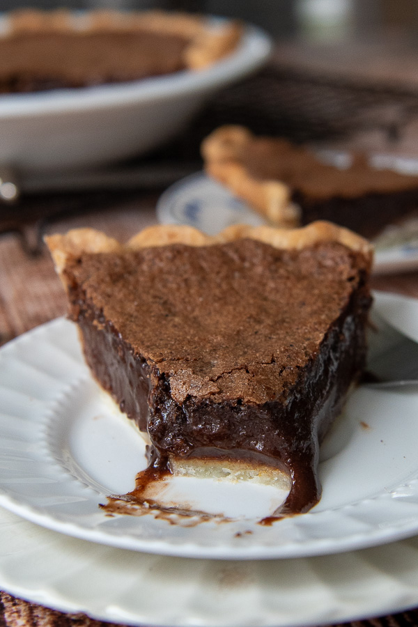 a piece of chocolate chess pie with a bit taken out