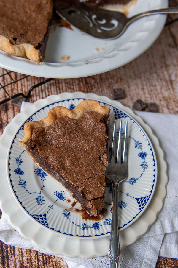 overhead shot of chocolate chess pie on a blue and white plate with fork resing on it