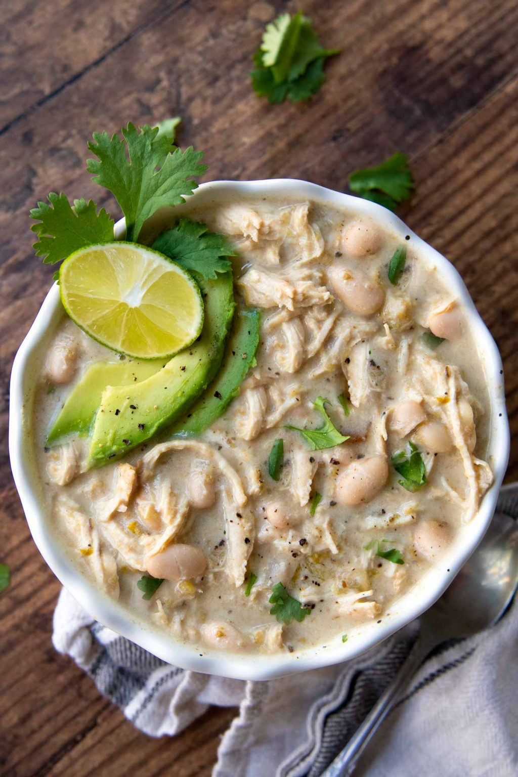 overhead shot of instant pot white chicken chili with sliced avocados, cilantro, and lime wedge on top