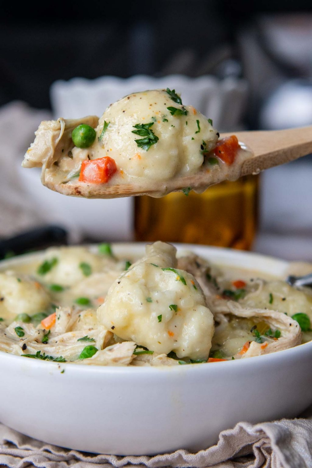 a wooden spoon holding up a scoop of chicken and dumplings