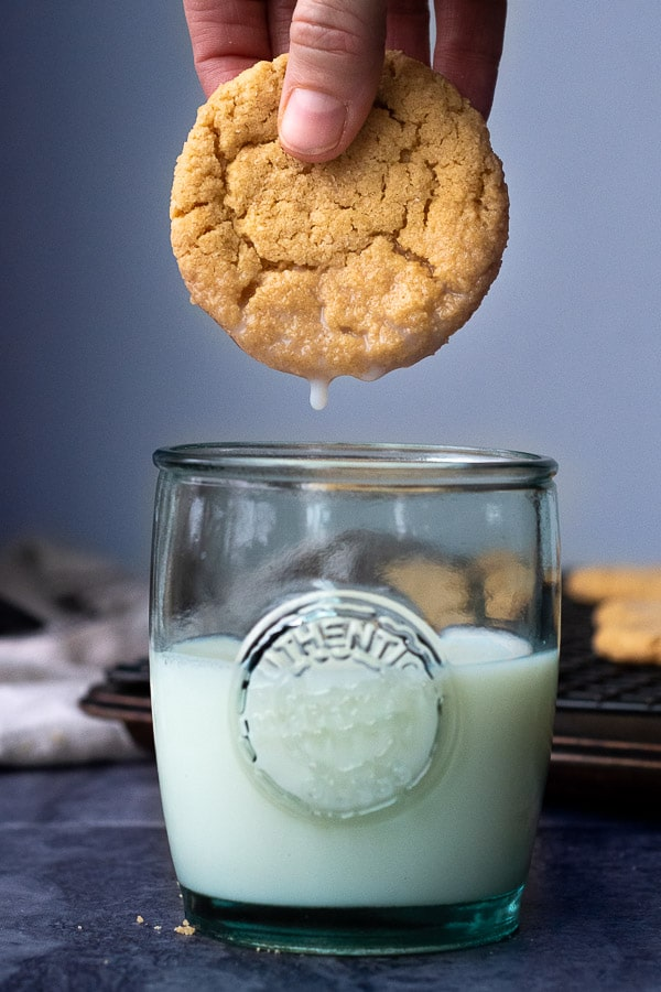 a cookie being dunked into a glass of milk