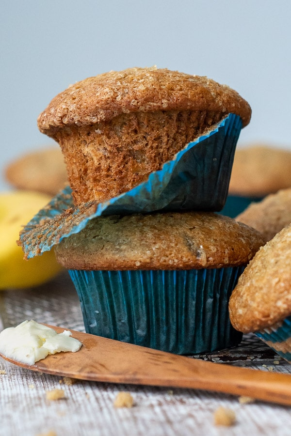 a stack of 2 muffins with a blue muffin paper coming off one