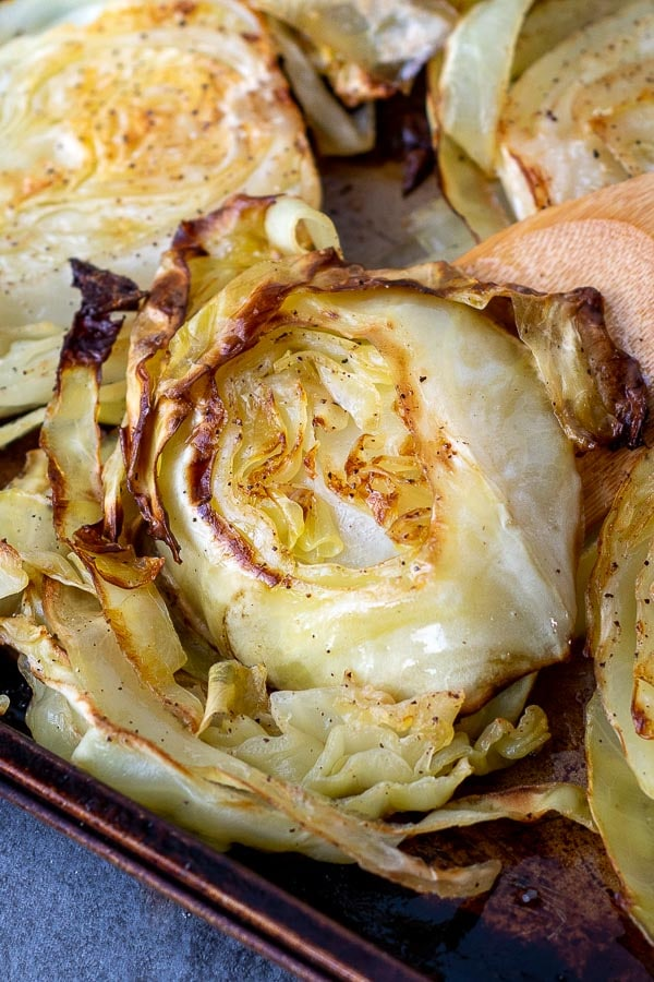 a close up of roasted cabbage on a baking sheet