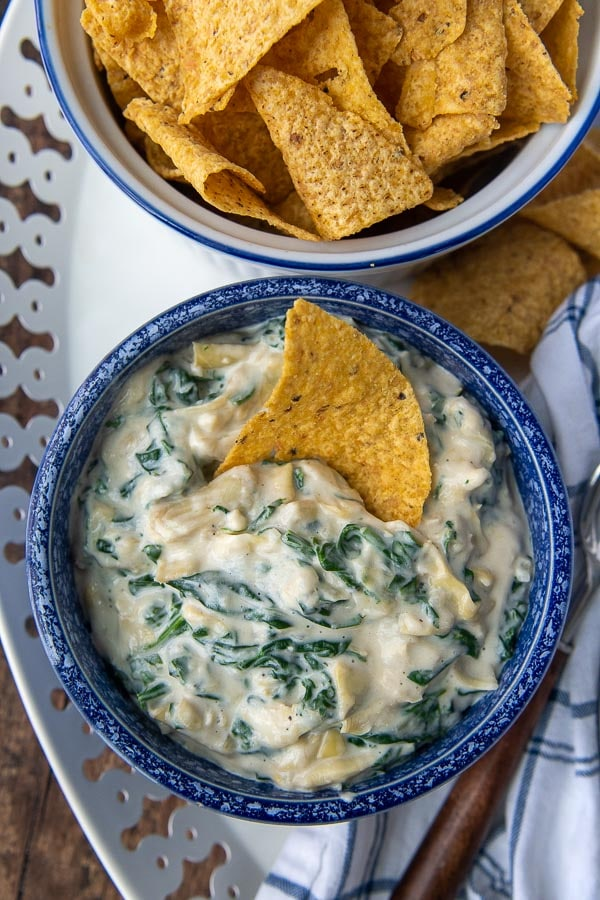 overhead shot of spinach artichoke dip with bowl of tortilla chips next to it
