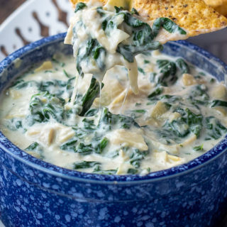a tortilla chip lifting out a scoop of spinach artichoke dip from a blue bowl