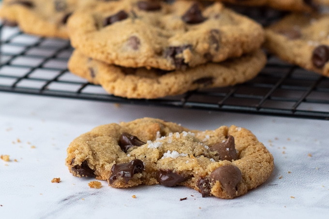 a bitten almond flour chocolate chip cookie with cookies cooling in back