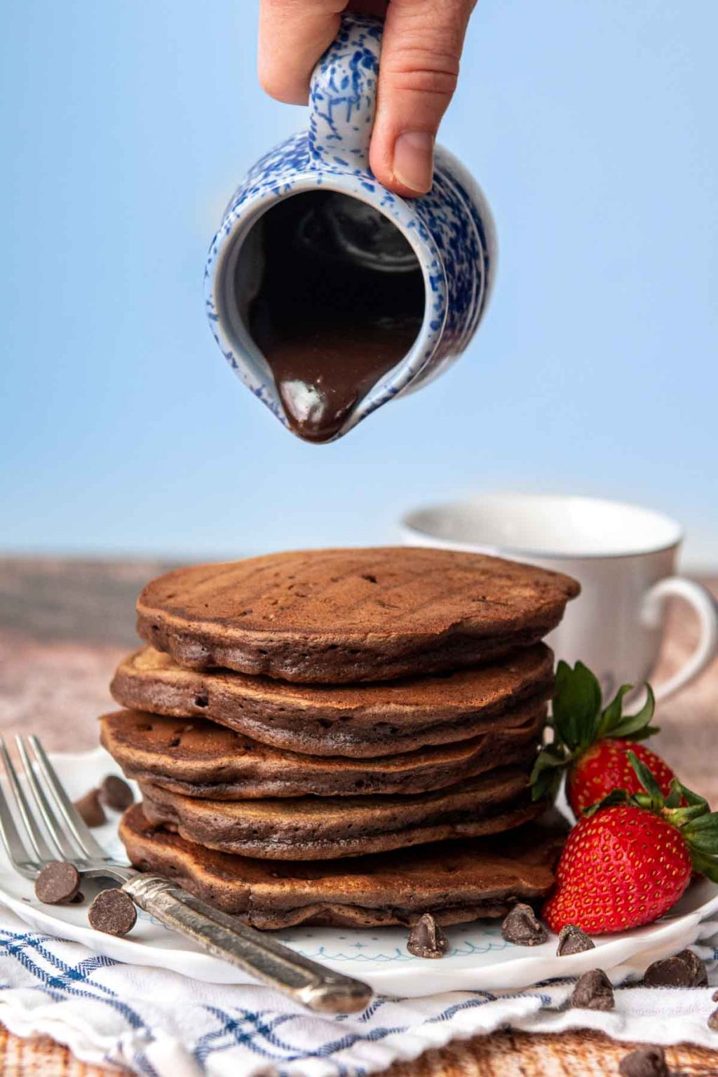 chocolate syrup about to go on a stack of chocolate pancakes