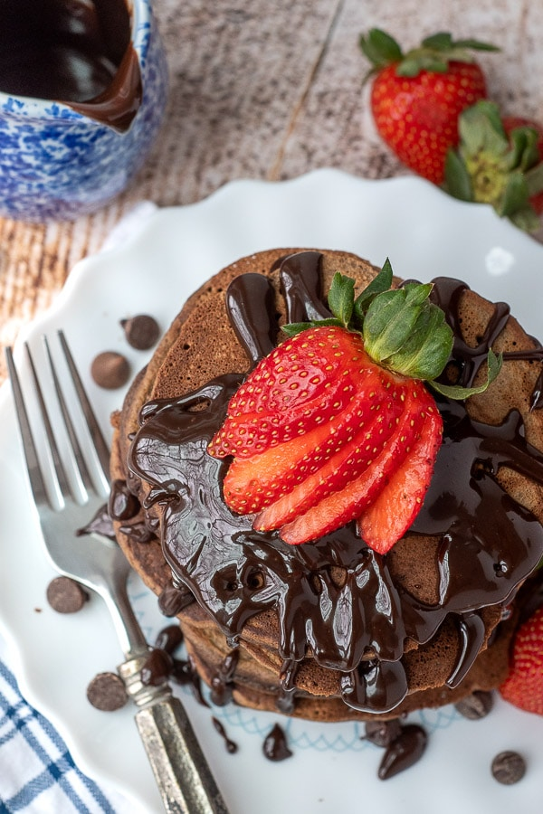overhead shot of chocolate chocolate chip pancakes with hot fudge and strawberries