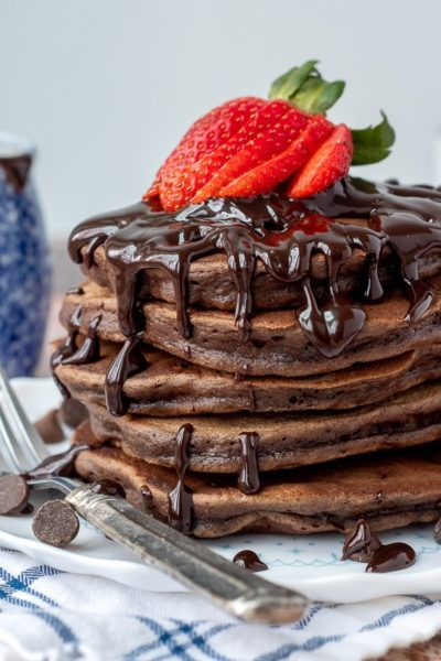 stack of double chocolate pancakes with hot fudge and strawberries on top