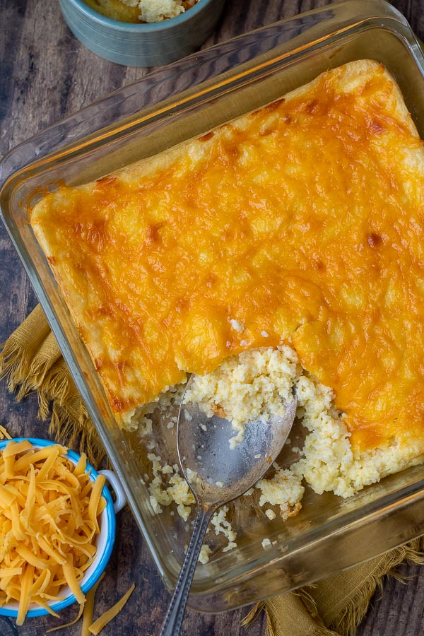 overhead shot of cheese grits casserole with shredded cheese next to it