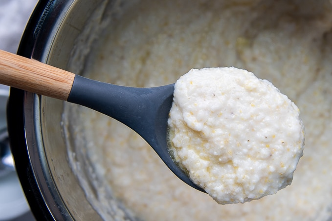a ladle holding up a serving of grits from an instant pot