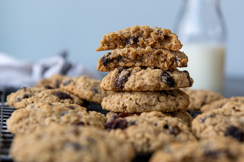 a stack of oatmeal raisin cookies on a cooking rack with the top one split open