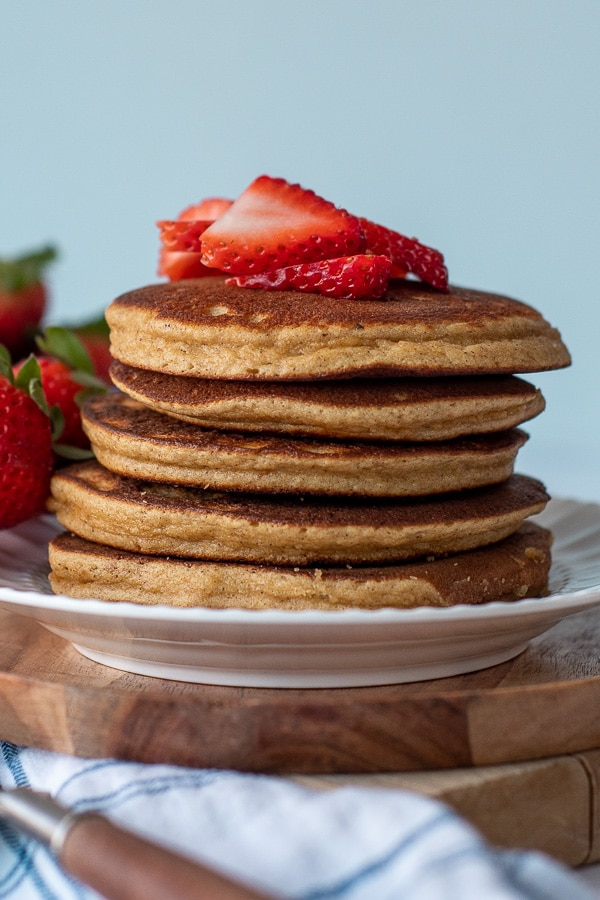 a stack of pancakes with almond flour on white plate with sliced strawberries on top