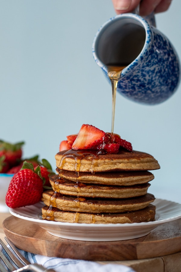 syrup being poured over a stack of almond flour pancakes