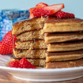 a stack of pancakes made with almond flour that are cut and syrup drizzling down