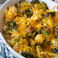 close up of melted cheese on broccoli and cauliflower in a casserole dish
