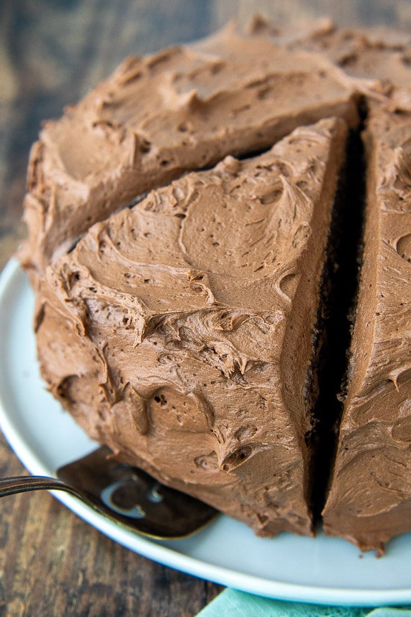 chocolate buttercream cake with a large slice about to be taken out