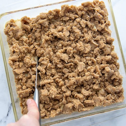 a knife cutting through crumb topping to swirl