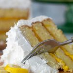 a fork cutting into slice of coconut cake with lemon filling