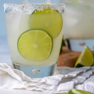 straight on shot of limeade margarita with lime slices next to it