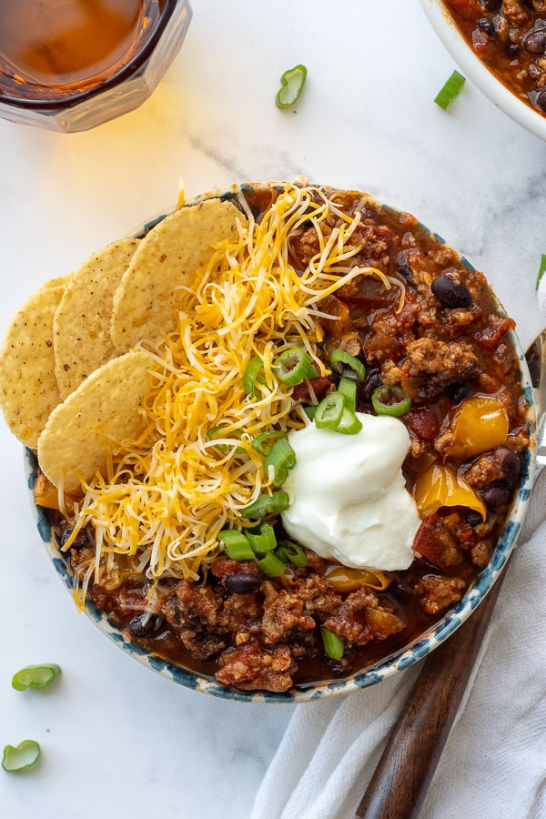 overhead shot of turkey chili in a bowl with sour cream and chips