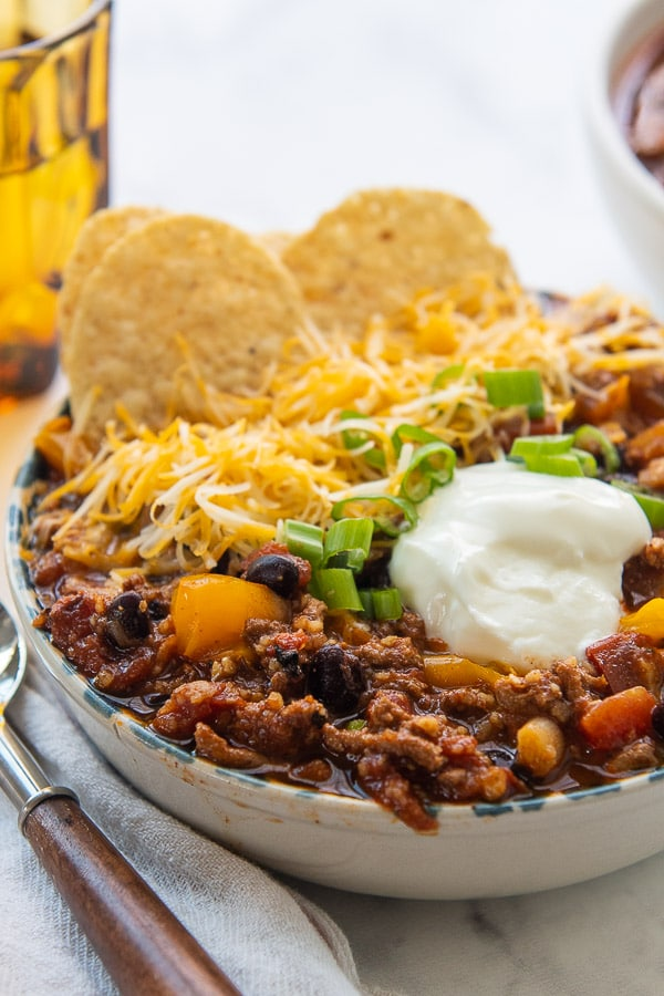 side angle close up of chili in a bowl with spoon and glass next to it