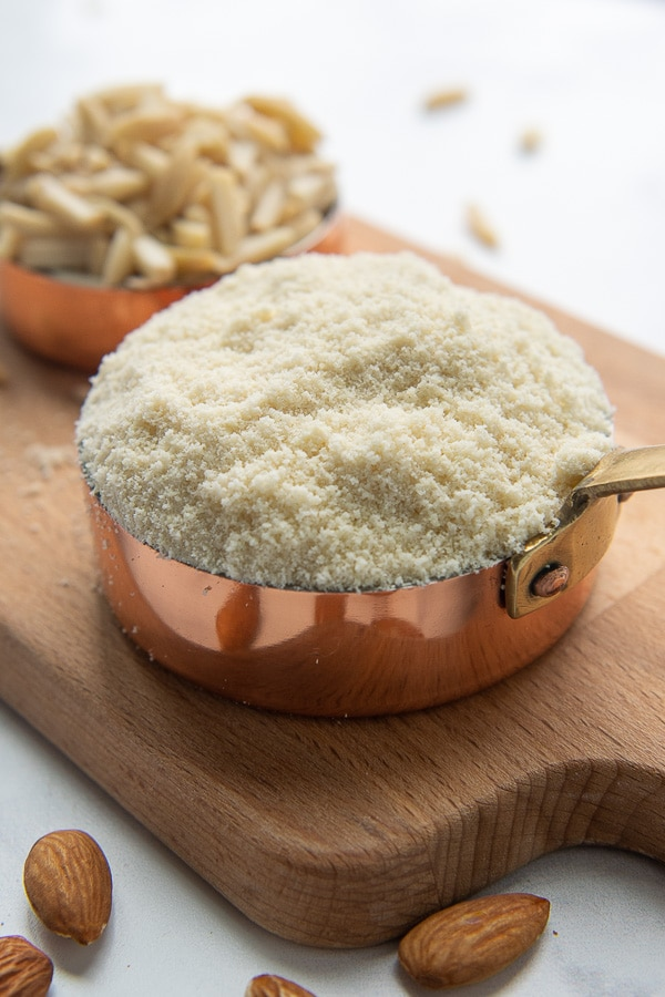 a measuring cup full of almond flour on a wooden cutting board