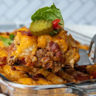 a spatula lifting bacon cheeseburger casserole from a baking dish